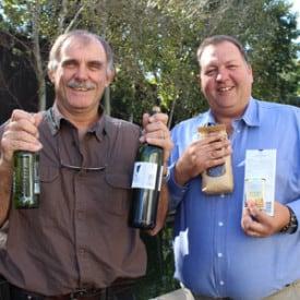 Dr. Gerhard Verdoorn en mnr. Kobus Steenekamp met bier, wyn, koffie, sigarette en sjokolade vas wat volgens die IARC kanker kan veroorsaak. Foto. Nico van Burick
